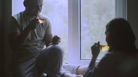 Окно молодой счастливый обнимать пар стоящее близко и наслаждаться взглядом от новой квартиры сток-видео