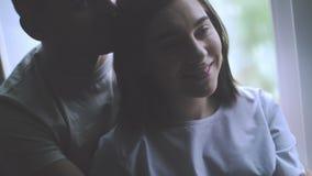 Окно молодой счастливый обнимать пар стоящее близко и наслаждаться взглядом от новой квартиры видеоматериал