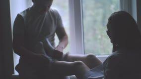 Окно молодой счастливый обнимать пар стоящее близко и наслаждаться взглядом от новой квартиры акции видеоматериалы