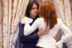 Окно молодой женщины embrace человека близко curtained Стоковые Изображения RF