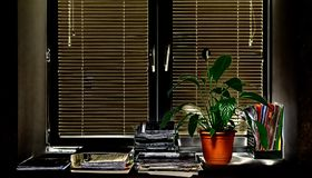 Окно офиса взгляда темное с закрытыми шторками расположенными на windowsill стоковые изображения rf