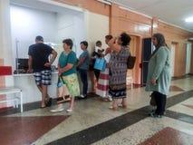 Окно регистратуры в клинике района Очередь больных посетителей Стоковое Изображение RF