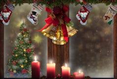 Окно рождества, свечи, колоколы золота, чулки, украшения дерева, предпосылка снега для поздравительной открытки стоковое изображение