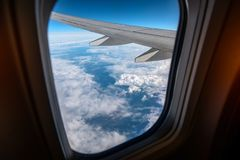 Окно самолета from inside До окно вы можете увидеть облака и крыло самолета Стоковое Фото