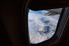 Окно самолета from inside До окно вы можете увидеть облака и крыло самолета Стоковое Изображение