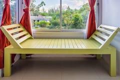 Окно современной зеленой деревянной скамьи близрасположенное Стоковое Изображение RF