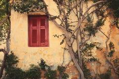 Окно с красной штаркой Anafiotika в городке Афин, Греции. Стоковое Фото