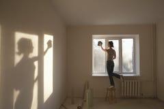 Окно чистки женщины в новой квартире стоковые фотографии rf