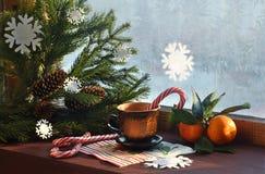 Окно Snowy и ветви рождественской елки, горячего питья, конфеты и tangerines Стоковые Изображения RF