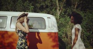 Около винтажные оранжевые девушек шины 2 харизматических африканских и белокурого одного, фотографирующ от винтажной камеры фото видеоматериал
