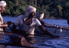 Около Port Blair, Андаманские острова, Индия, около октябрь 2002: Рыболовы вытягивая fishnet от океана стоковое фото rf