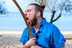 Околпачивать вокруг бородатого человека в голубых кимоно, плюшке и ручках на главной лижа шпаге стоковые фотографии rf
