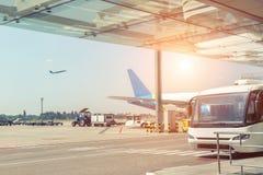Окружающая среда и обслуживания аэропорта Пассажиры пригородного автобуса ждать на здании терминала Большой коммерчески самолет д стоковые изображения