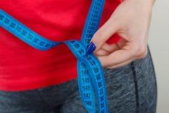 Окружность талии женщины измеряя с лентой стоковое изображение