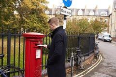 ОКСФОРД ВЕЛИКОБРИТАНИЯ 26-ОЕ ОКТЯБРЯ 2016: Письмо оприходования человека в королевском Postbox почты стоковое фото