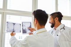 2 доктора анализируя изображение рентгеновского снимка Стоковая Фотография