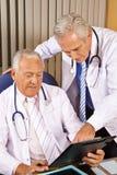 2 доктора говоря о контрольном списоке Стоковая Фотография RF