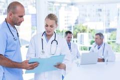 2 доктора держа доску сзажимом для бумаги пока их работа коллег Стоковое Изображение RF