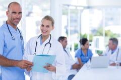 2 доктора держа доску сзажимом для бумаги пока их работа коллег Стоковые Фото