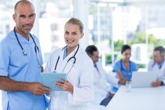 2 доктора держа доску сзажимом для бумаги пока их работа коллег Стоковые Изображения