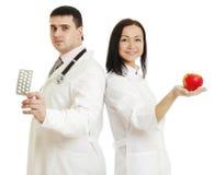 2 доктора держа яблоко и пилюльки - изображение запаса Стоковая Фотография RF