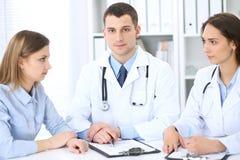 2 доктора и пациент сидя на таблице в медицинском шкафе Стоковая Фотография