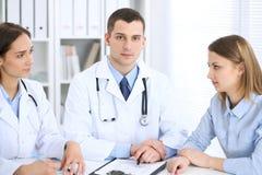2 доктора и пациент сидя на таблице в медицинском шкафе Стоковое Изображение RF