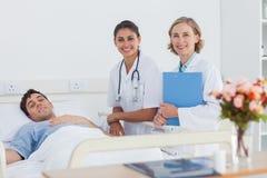 2 доктора и пациент смотря камеру Стоковые Фото