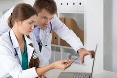 2 доктора медицины смотря монитор компьтер-книжки Стоковое Изображение