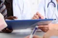 2 доктора обсуждают документ на пусковой площадке доски сзажимом для бумаги Стоковые Изображения RF