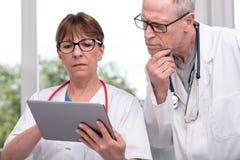 2 доктора обсуждая о медицинском заключении на таблетке Стоковые Изображения