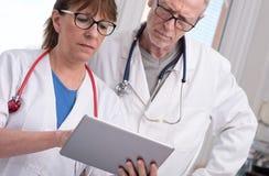 2 доктора обсуждая о медицинском заключении на таблетке Стоковое Фото