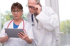 2 доктора обсуждая о медицинском заключении на таблетке Стоковая Фотография