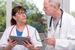 2 доктора обсуждая о медицинском заключении на таблетке Стоковое фото RF