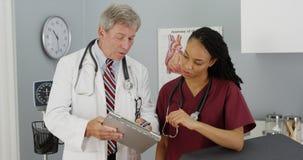 2 доктора обсуждая результаты пациента Стоковые Изображения