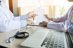 2 доктора обсуждая терпеливые примечания в офисе указывая к a Стоковые Фото