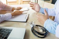 2 доктора обсуждая терпеливые примечания в офисе указывая к a Стоковое фото RF