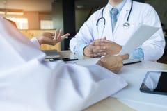 2 доктора обсуждая терпеливые примечания в офисе указывая к a Стоковые Изображения RF