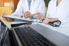 2 доктора обсуждая терпеливые примечания в офисе указывая к a Стоковые Фотографии RF
