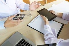 2 доктора обсуждая терпеливые примечания в офисе указывая к a Стоковое Фото