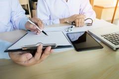 2 доктора обсуждая терпеливые примечания в офисе указывая к a Стоковая Фотография RF