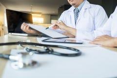 2 доктора обсуждая терпеливые примечания в офисе указывая к a Стоковое Изображение