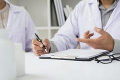 2 доктора обсуждая терпеливые примечания в офисе указывая к a Стоковая Фотография