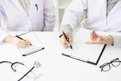 2 доктора обсуждая терпеливые примечания в офисе указывая к a Стоковое Изображение RF