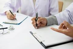 2 доктора обсуждая терпеливые примечания в офисе указывая к a Стоковые Изображения