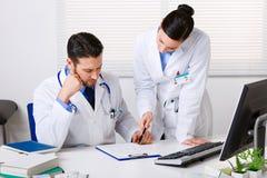 2 доктора обсуждая терпеливые примечания в офисе Стоковая Фотография RF