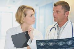 2 доктора обсуждая терпеливые рентгеновские снимки на больнице Стоковые Фотографии RF
