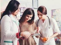 2 доктора показывая продукты в каталоге к клиенту Стоковое Изображение