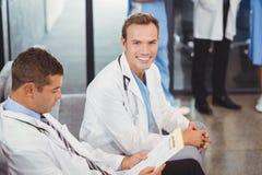 2 доктора при доска сзажимом для бумаги сидя на софе Стоковые Фото
