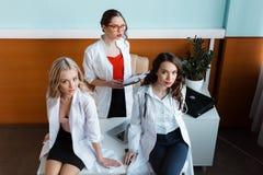 3 доктора сидя на таблице в шкафе Стоковая Фотография